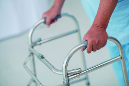 Close-up of male patient moving with walker